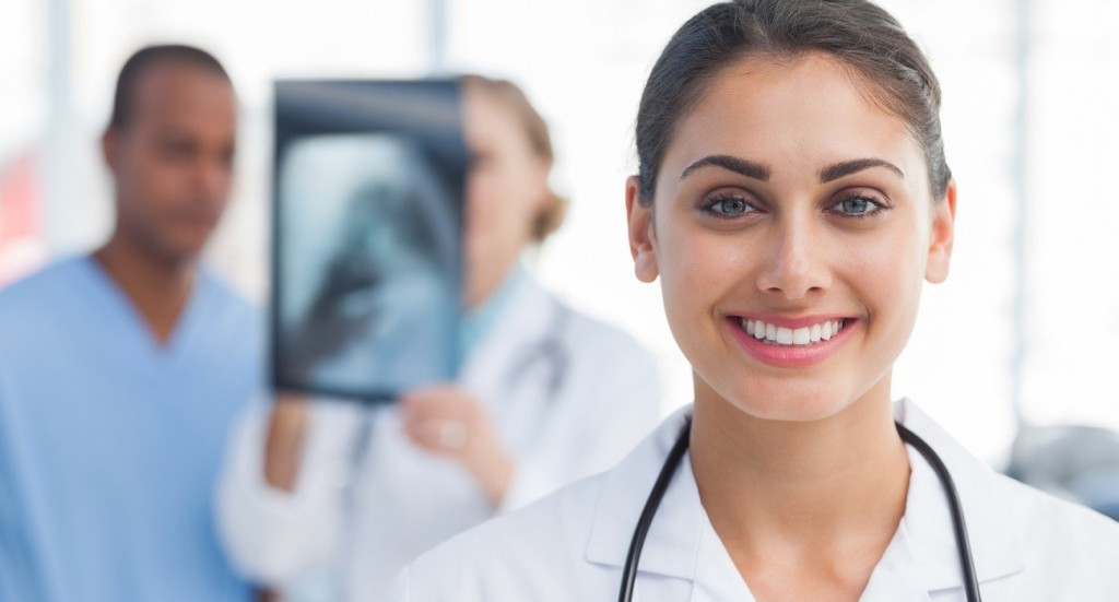 Smiling doctor standing in front of medical team analysing an x-ray