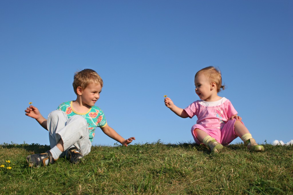 children on grass with flowers